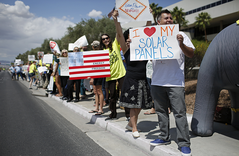 Ronald Brittan, right, and others demonstrate in favor of solar energy in front in Las Vegas, Nevada.